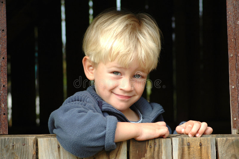 Boy looking out of window. A beautiful clever blond caucasian white boy child head portrait with happy smiling and smart expression in his handsome face looking royalty free stock images
