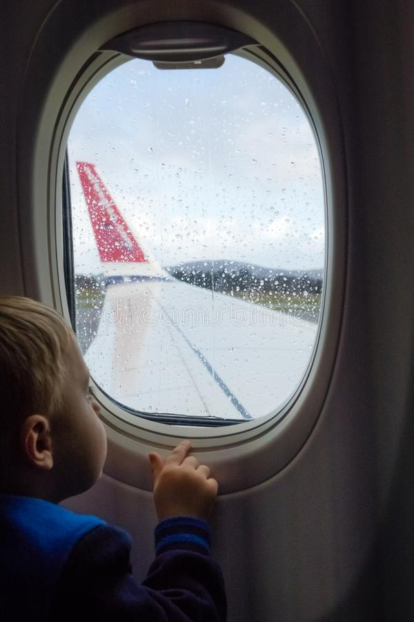 Boy looking through the plane window royalty free stock photo