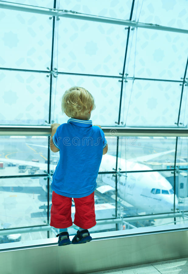 Boy looking at planes in the airport stock image