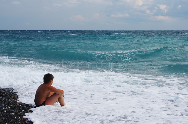 Boy looking at sea stock photography