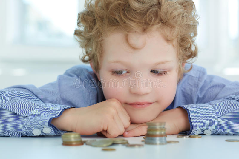 Boy looking at a stack of coins. The concept of children`s economic education. Boy looking at a stack of coins royalty free stock image
