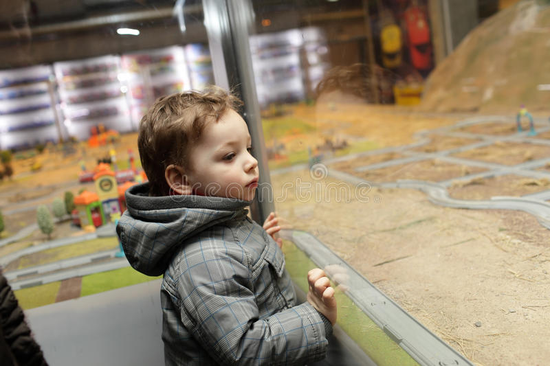 Boy looking at toy town. In the indoor playground royalty free stock photo