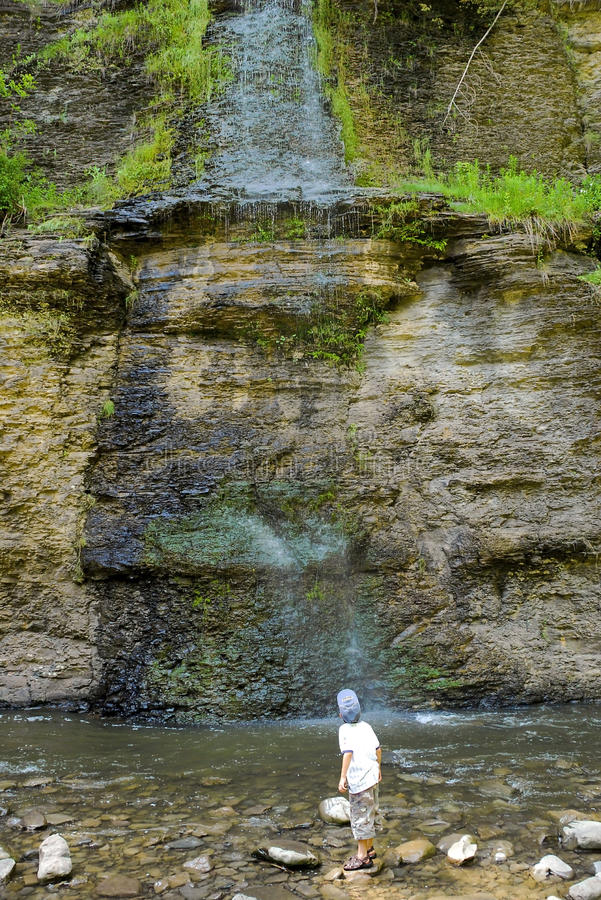 Boy Looking Up At Cliffs Trickling Waterfall. Boy standing in stream looking up at slow trickle of water over shale rock layer cliffs at Mine Kill Falls State stock image