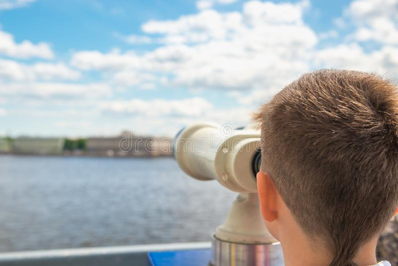 Boy looks at binoculars on sights of the city. Travel, tourism, royalty free stock photography