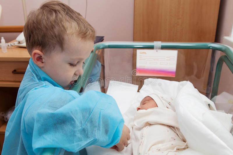 Brother and sister. The boy looks at his newborn sister in the maternity hospital royalty free stock photography