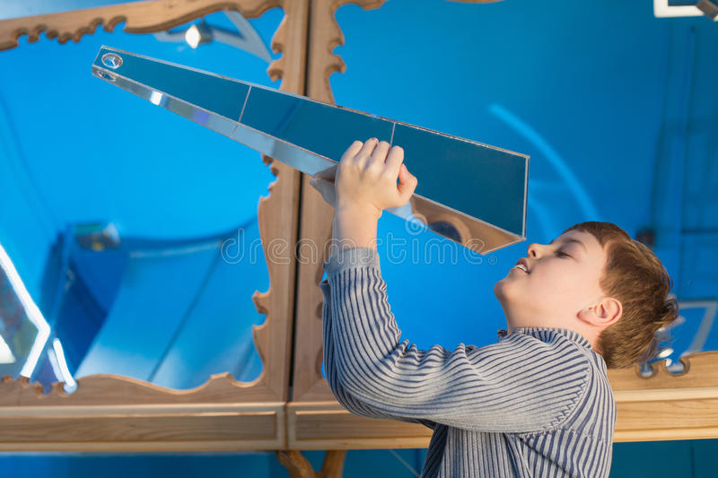 The boy looks at Nick Moores Kaleidosphere. The Kaleidosphere is a modern 3D Kaleidoscope. With obelisk shapes, inspired from Nick Moores larger museum royalty free stock photography