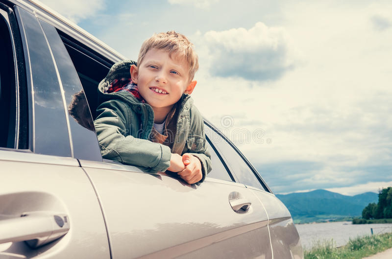 Boy looks out from car window royalty free stock image