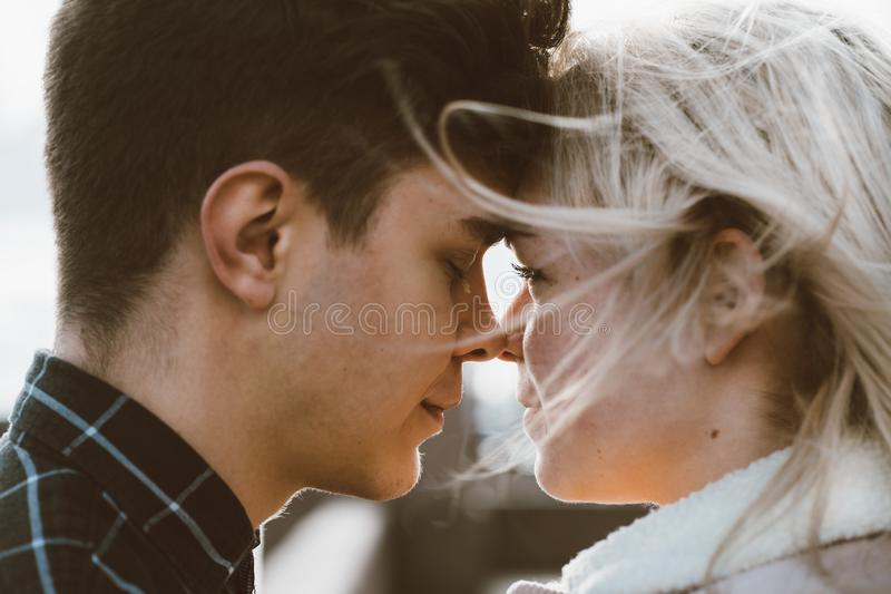 The boy looks tenderly at girl and wants to kiss. A young couple stands embracing. The concept of teenage love and first kiss, royalty free stock photos