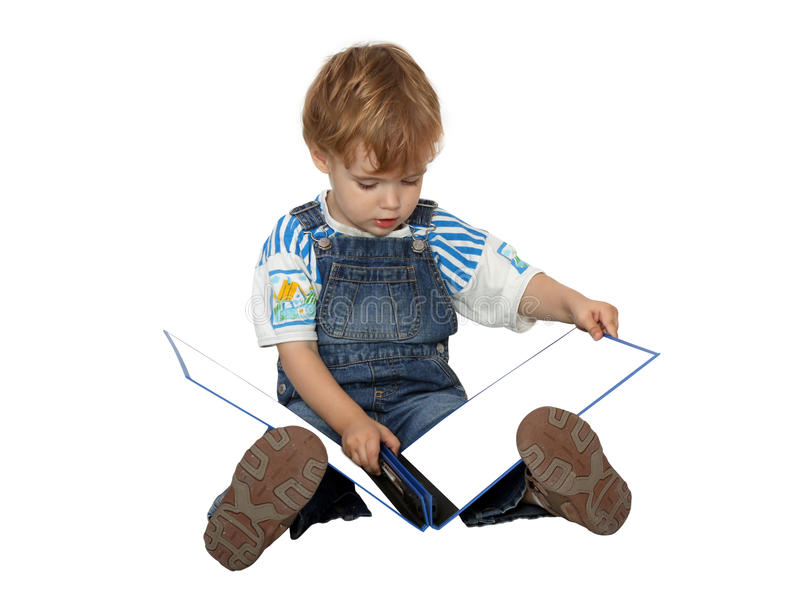 The boy looks on white pages in blue album royalty free stock photography