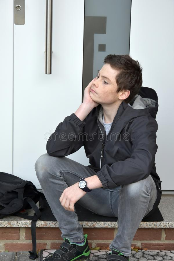 Boy is waiting for someone with front door key. Boy lost or forgot the latchkey, now he sits in front of the door and has to wait until his parents will come royalty free stock photos