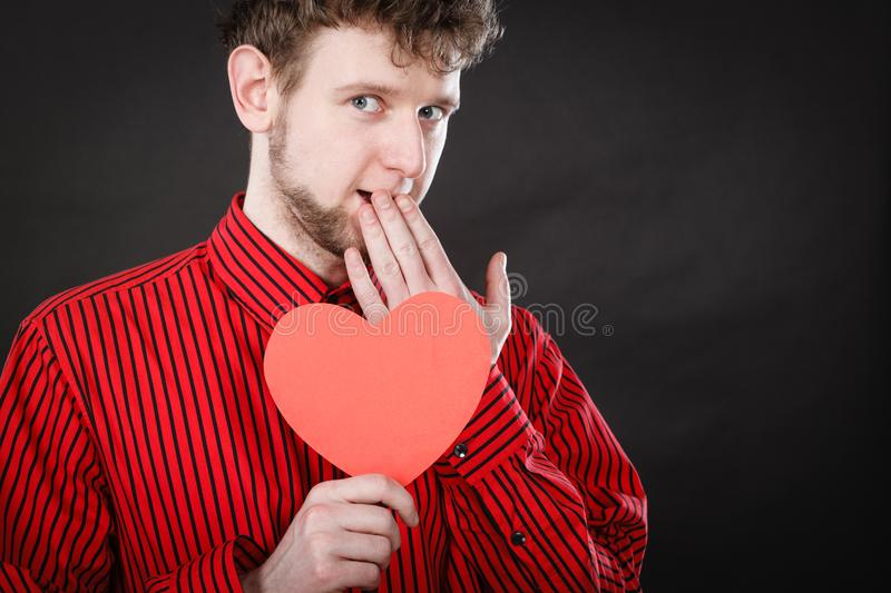 Boy in love with red heart. Love and help from people. Charming lovely man with red paper heart persuade to be good helpful hopeful. Valentines Day or charity royalty free stock image
