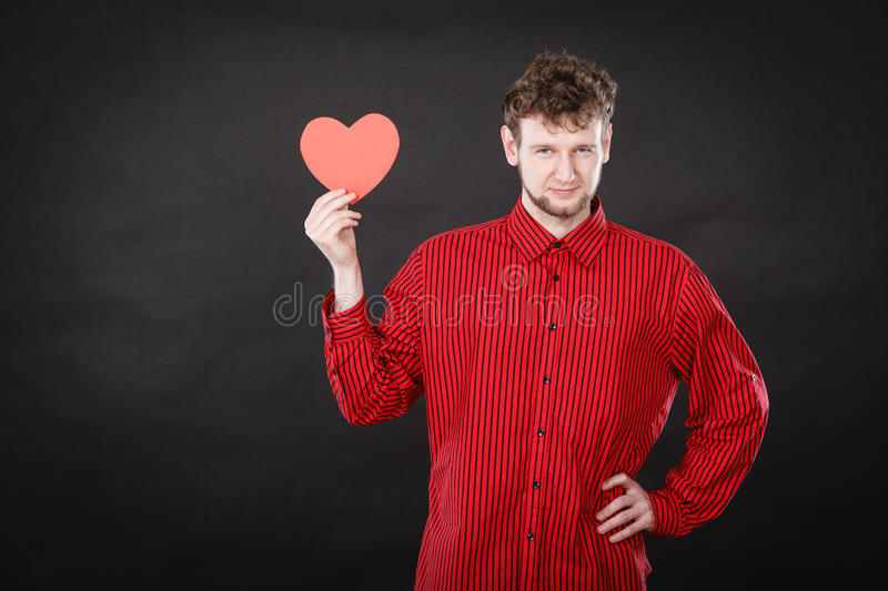 Boy in love with red heart. Love and help from people. Charming lovely man with red paper heart persuade to be good helpful hopeful. Valentines Day or charity royalty free stock images
