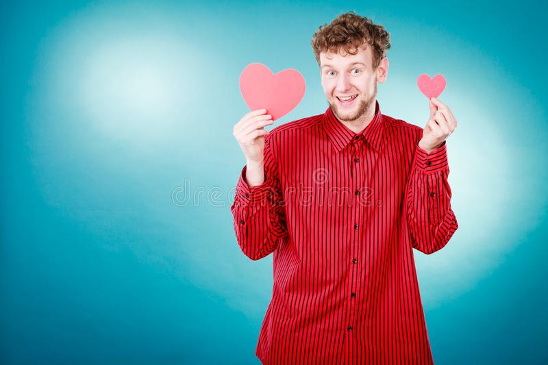 Boy in love with red heart. Love and help from people. Charming lovely man with two red paper hearts persuade to be good helpful hopeful. Valentines Day or royalty free stock photos