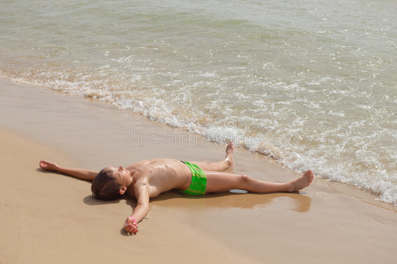 Boy lying on the beach and sunning stock photography