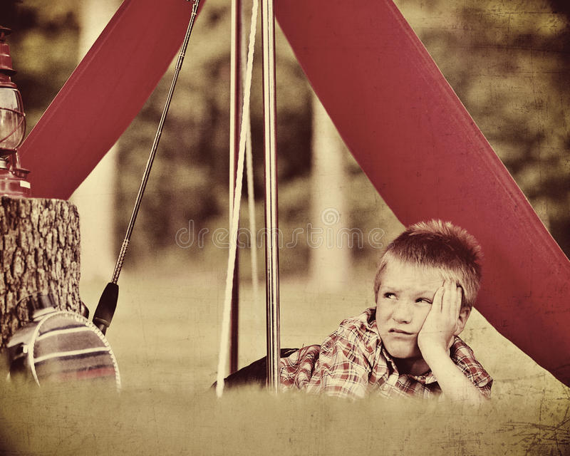 Boy lying down in a tent. Looking puzzled and unhappy stock photos