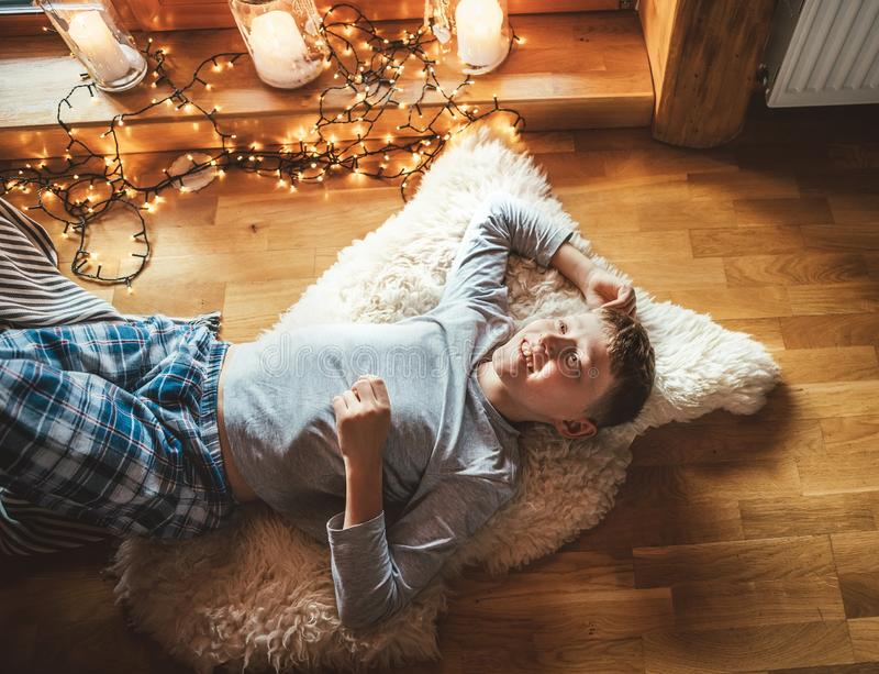 Boy lying on floor on sheepskin and looking in window in cozy home atmosphere. Peaceful moments of cozy home concept image royalty free stock images