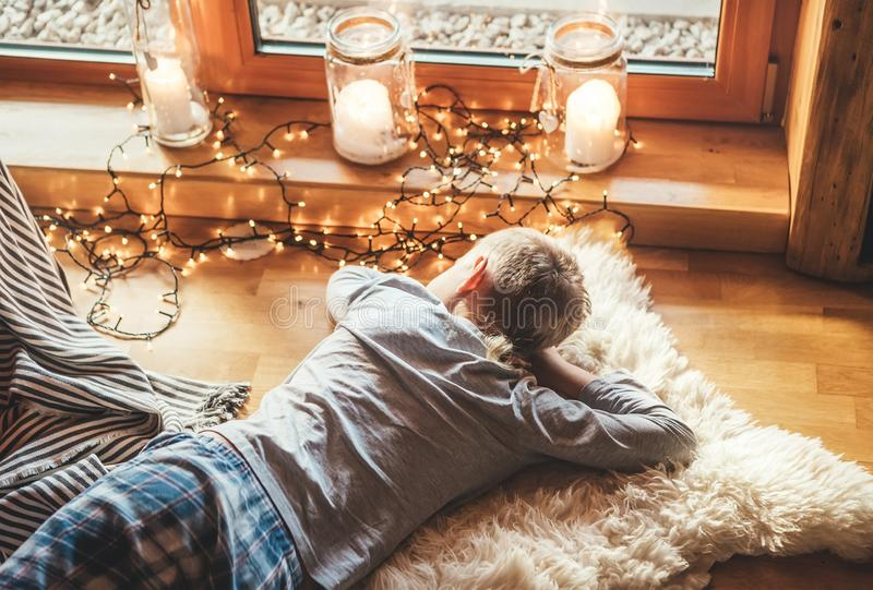 Boy lying on floor on sheepskin and looking in window in cozy home atmosphere. Peaceful moments of cozy home concept image stock image