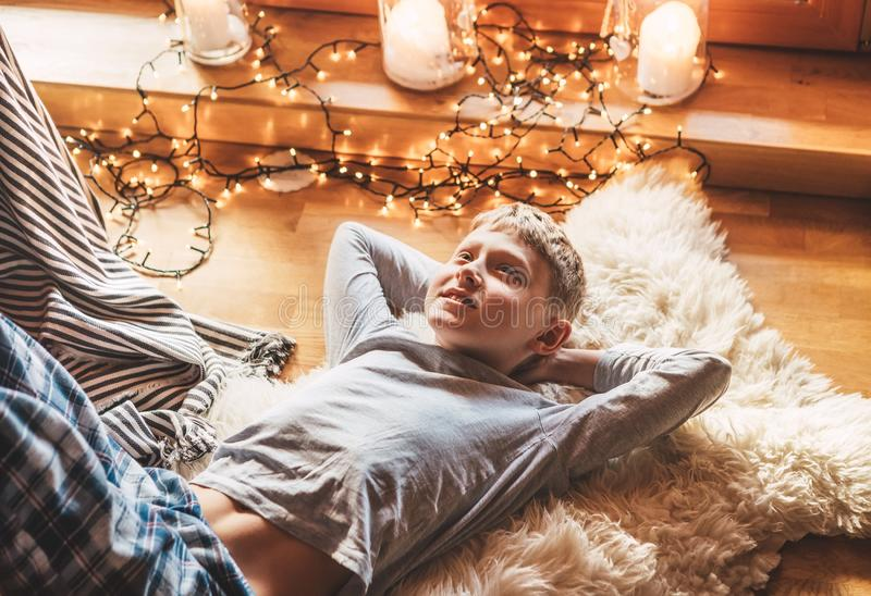 Boy lying on the floor and smiling on sheepskin in cozy home atmosphere and dreaming about Christmas presents. Peaceful moments of stock photo