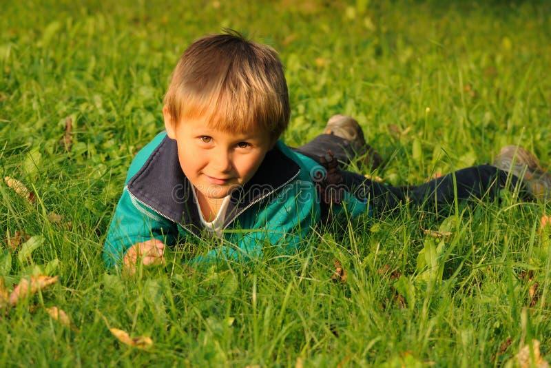 Boy lying on grass stock photos