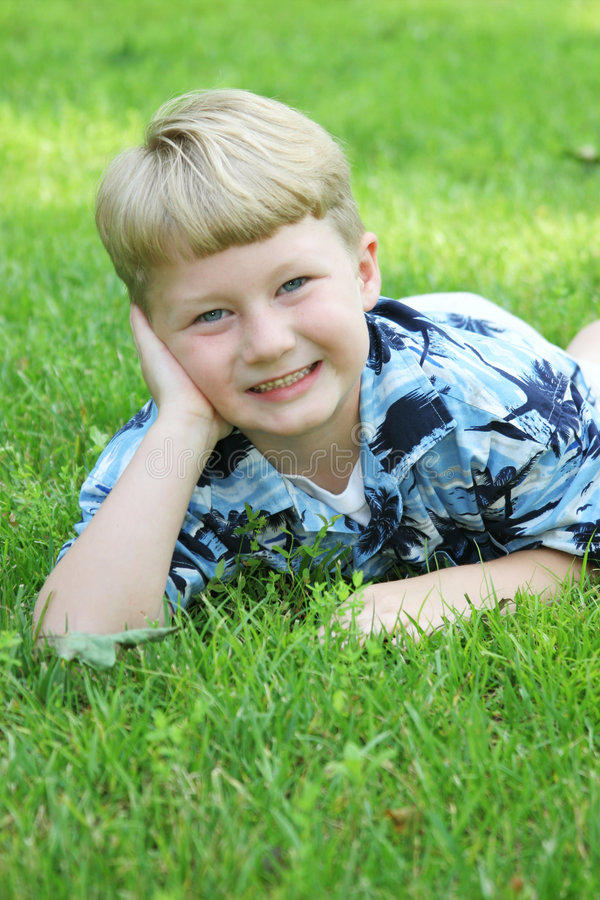 Boy lying on grass royalty free stock photo