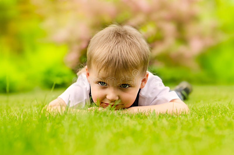 Boy lying on a green grass stock images