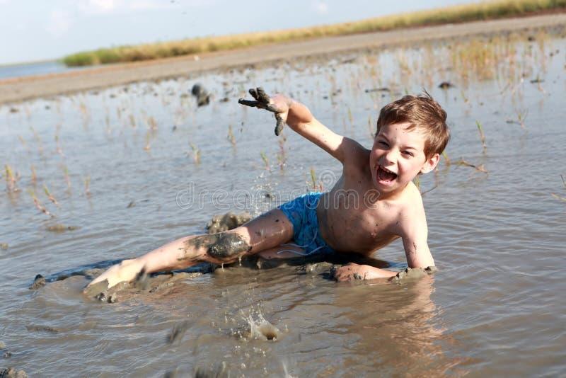 Boy lying in healing mud royalty free stock image