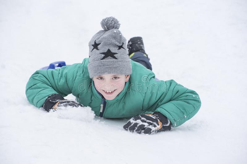 Boy lying in the snow on his belly and smiles. Portrait close-up stock photography