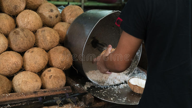 The boy made the coconut meat into shredded coconut stock photo