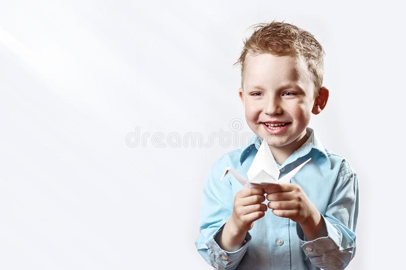 Boy made origami crane out of paper and rejoices on a light background royalty free stock photography