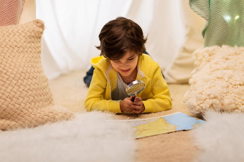 Boy with magnifier and map in kids tent at home royalty free stock images