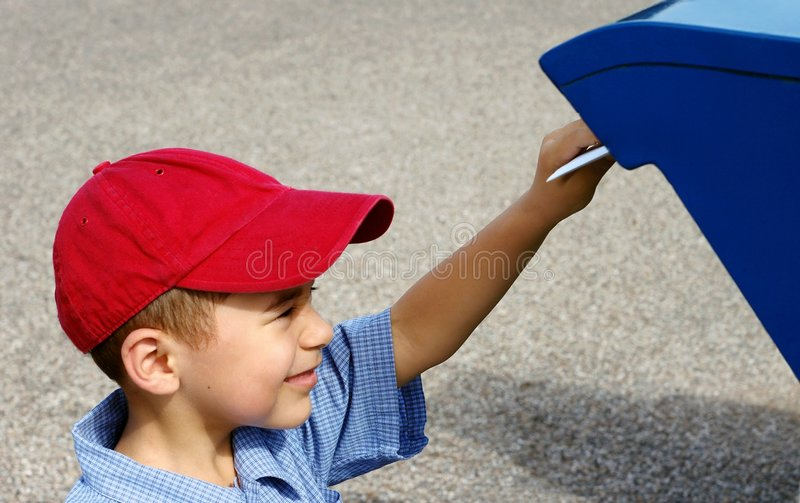 Boy mailing a letter. Horizontal scene of a young boy posting a letter royalty free stock photo