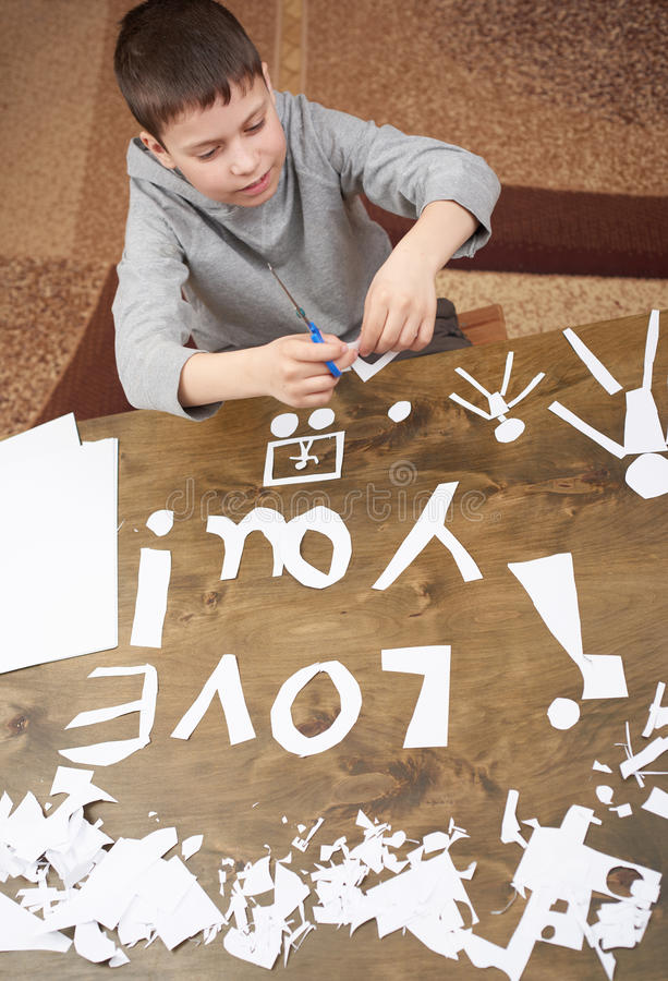 Boy makes origami - car and family, children, parent, I love you text, top view on wood background stock images