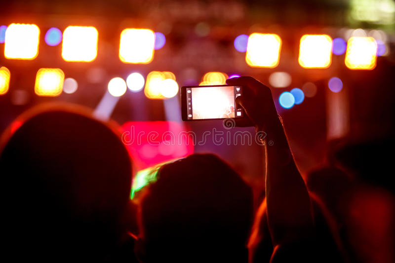 Boy makes photo with His smartphone to a concert share the moment friends on social networks. Boy makes photo with His smartphone to a concert to share the royalty free stock image