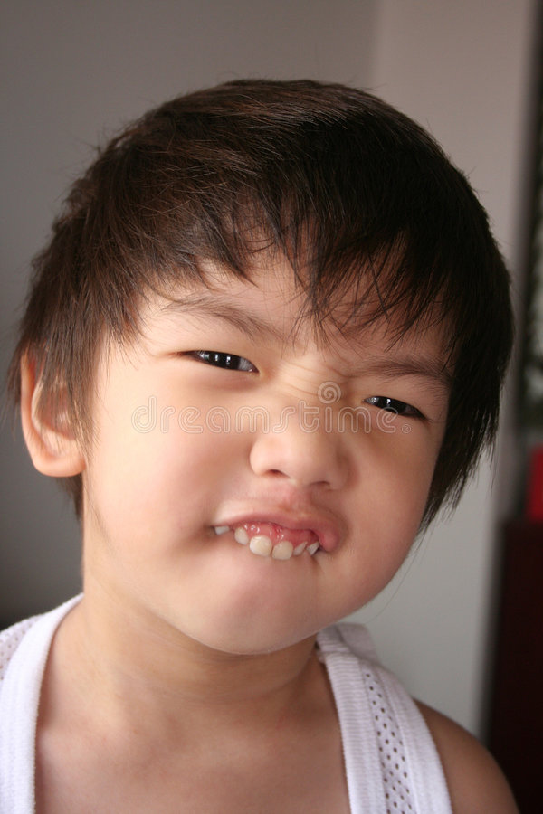 Boy making funny face. Boy biting on the lip making funny face royalty free stock image