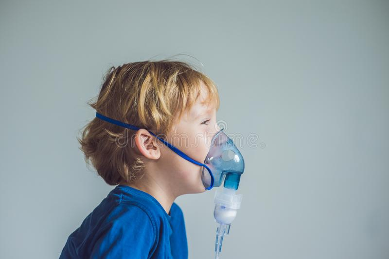 Boy making inhalation with a nebulizer at home.  stock images