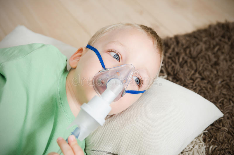Boy making inhalation with nebulizer at home. Child asthma inhaler inhalation nebulizer steam sick cough concept stock image