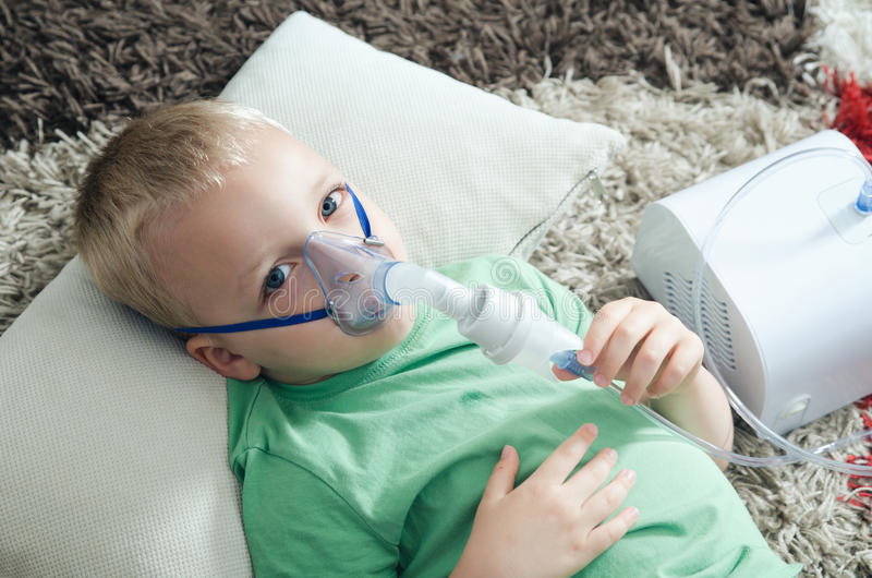 Boy making inhalation with nebulizer at home. Child asthma inhaler inhalation nebulizer steam sick cough concept stock photos