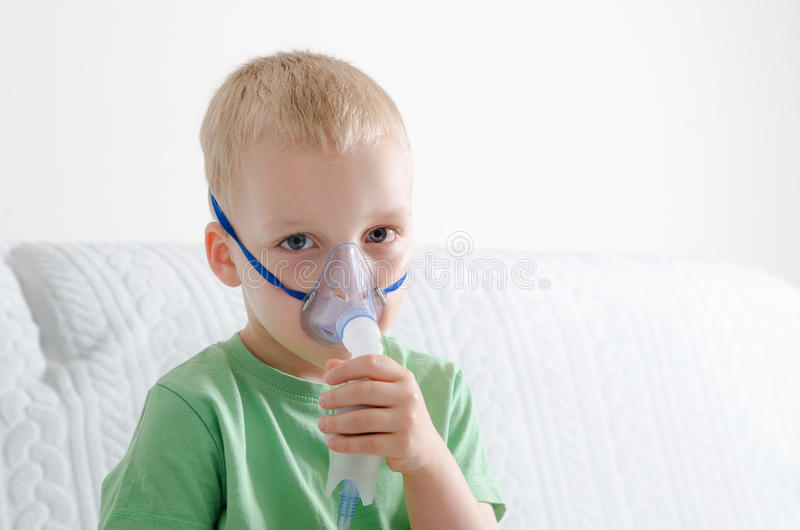 Boy making inhalation with nebulizer at home royalty free stock images