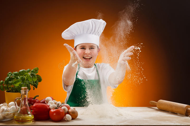 Boy making pizza dough. Boy making dough. Food ingredients on table stock photography