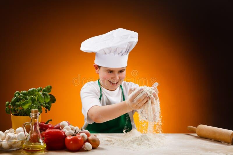 Boy making pizza dough. Boy making dough. Food ingredients on table royalty free stock photo