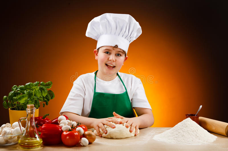Boy making pizza dough. Boy making dough. Food ingredients on table royalty free stock photos
