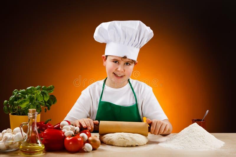 Boy making pizza dough stock image