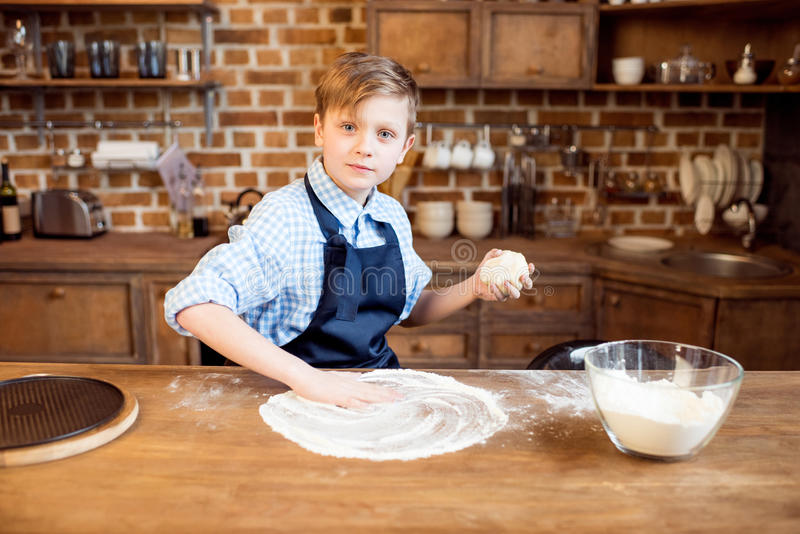 Boy making pizza dough on wooden tabletop in kitchen royalty free stock photography