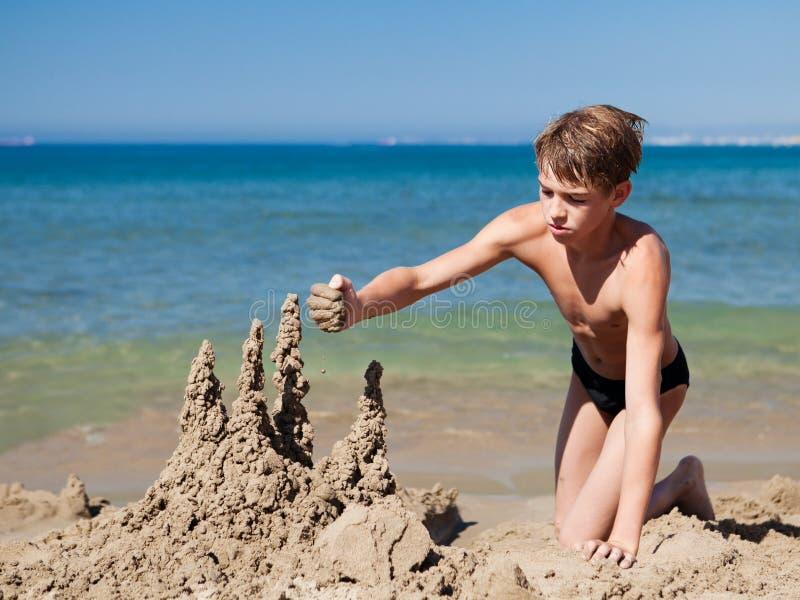 Boy making sand castle on beach stock photos