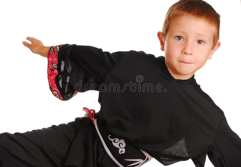 Boy in marital arts suit. Half body portrait of young boy in black marital arts suits practicing acrobatic kick, isolated on white background royalty free stock photos