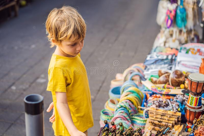 Boy at a market in Ubud, Bali. Typical souvenir shop selling souvenirs and handicrafts of Bali at the famous Ubud Market stock images
