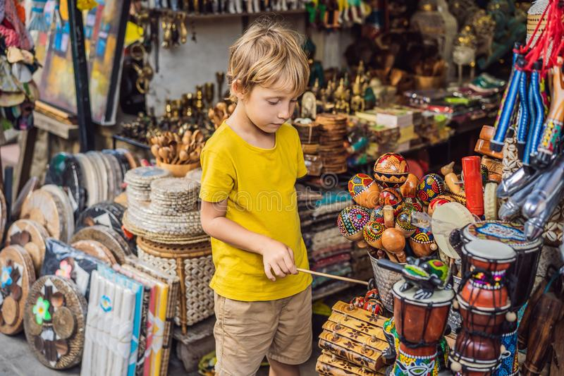 Boy at a market in Ubud, Bali. Typical souvenir shop selling souvenirs and handicrafts of Bali at the famous Ubud Market royalty free stock photos
