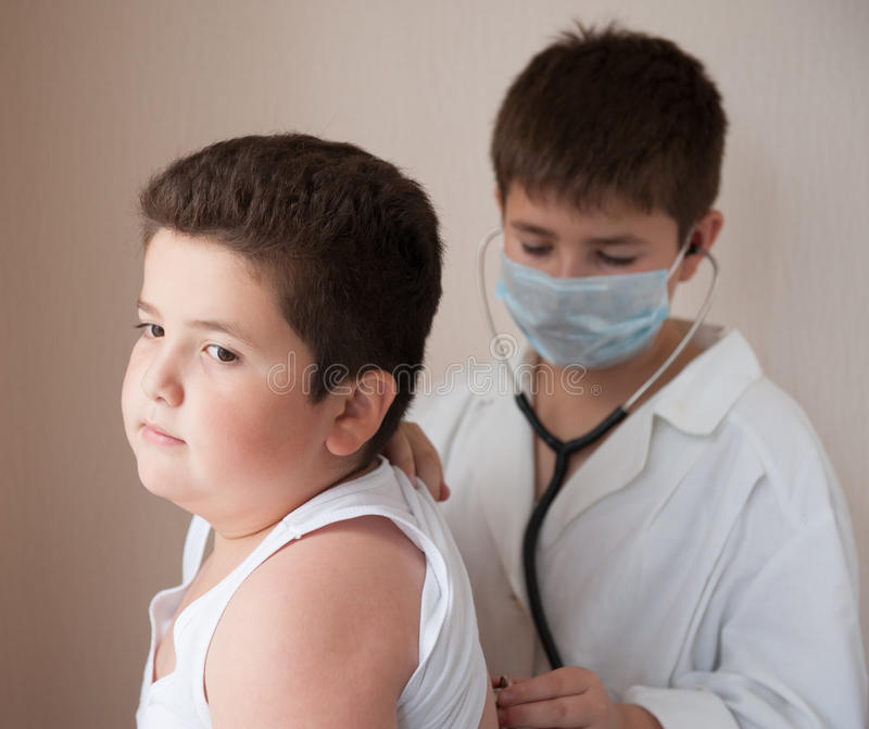 Boy in the mask and costume of the doctor listens to the heart rate of fat boy royalty free stock images