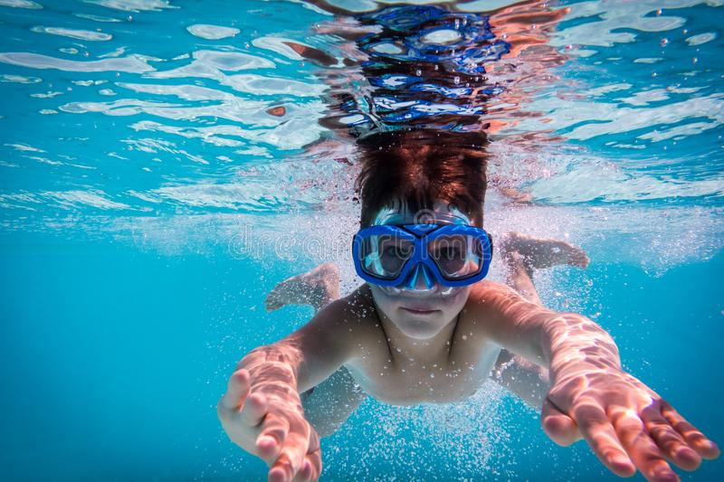 Boy in mask dive in swimming pool stock image