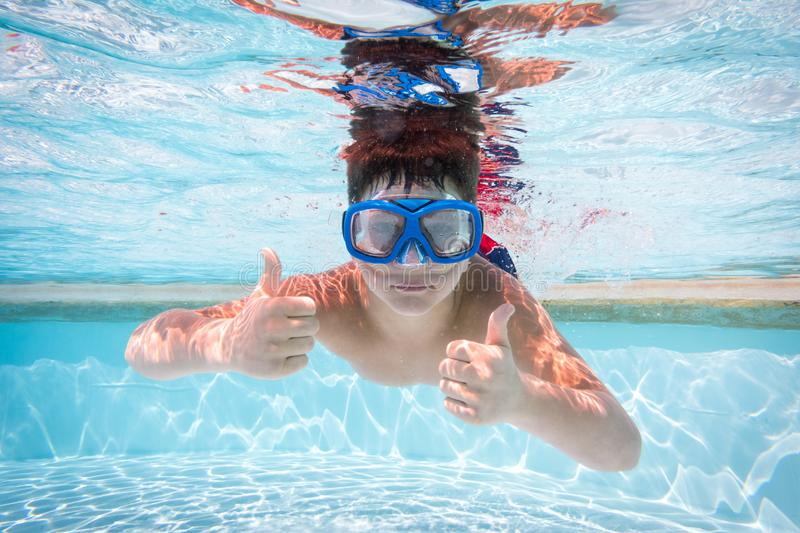 Boy in mask dive in swimming pool royalty free stock photos